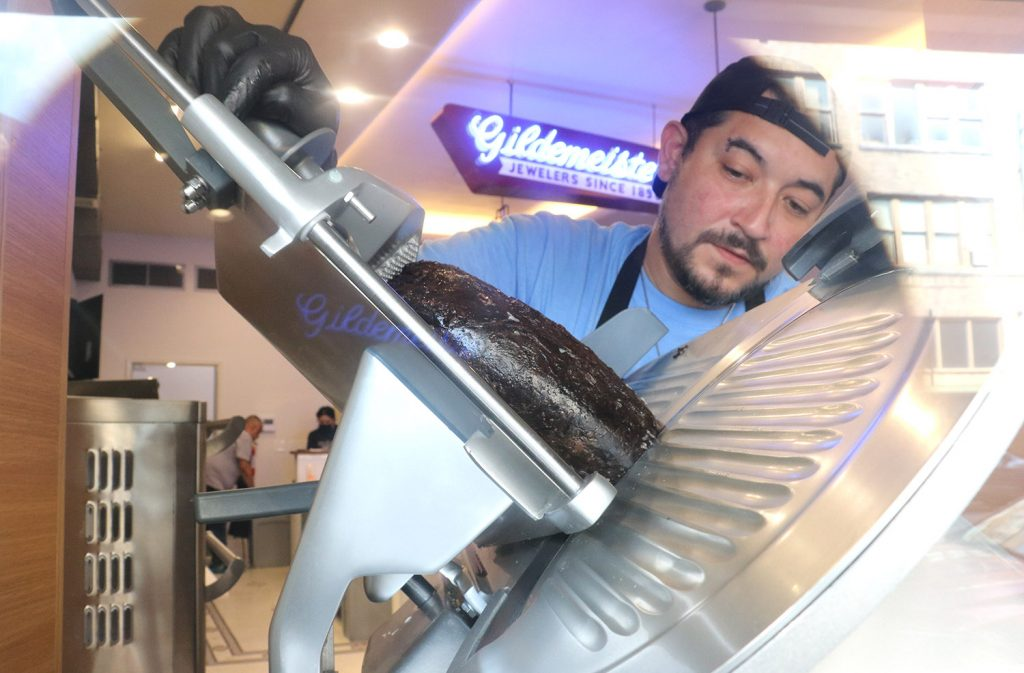 Broadway Delicatessen employee Chris Don slices pastrami in the morning of Sept. 2, 2021.